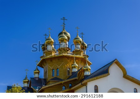 The golden dome on the  wooden russian church of the Holy Martyrs Faith, Hope and Charity and their mother Sophia in Belgorod, Russia. Close-up photo. - stock photo