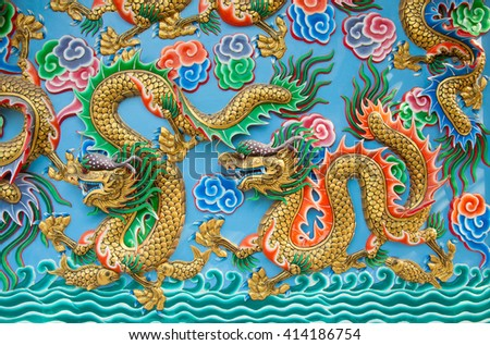 The golden dragon statue on blue wall at chinese temple
