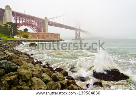 The Golden Gate Bridge as it goes over Fort Point and disappears into the fog on a typical San Francisco day - stock photo