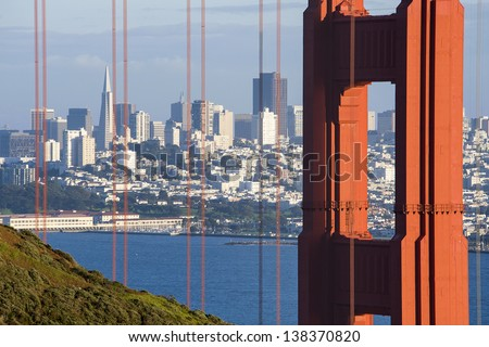 The Golden Gate bridge frames a view of San Francisco in the distance - stock photo