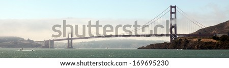 The Golden Gate Bridge shrouded in fog, as seen from the middle of San Francisco Bay. - stock photo