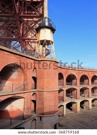 The Golden Gate Bridge towers over historic Fort Point in San Francisco. - stock photo