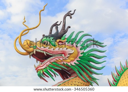 The golden great dragon statue with white cloud and blue sky