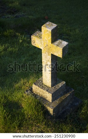 The golden light of the setting sun shining upon a gravestone cross in a cemetery in England, United Kingdom - stock photo