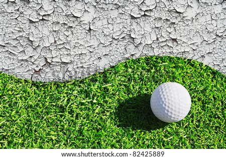 The golf ball lying on green grass and cracked earth - stock photo
