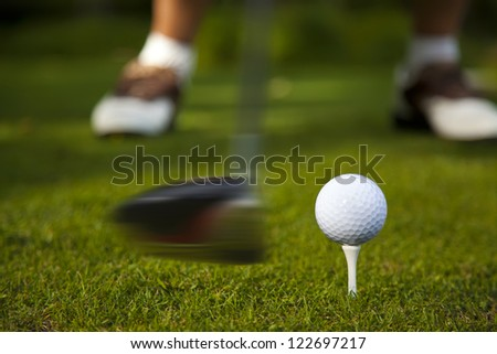 The golf club is captured in motion as it is about to strike the ball.
