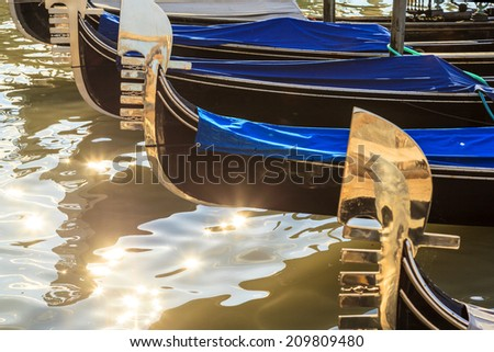 The Gondolas gondola in Venice with characteristic shape in the lagoon with other boats - stock photo