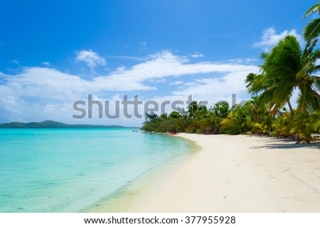 The gorgeous turquoise sea of Aitutaki lagoon viewed from the white sandy beach of the desert Ee Island, with coconut palm grove around. Cook Islands, South Pacific Ocean. - stock photo