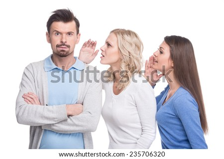 The gossip line. Two beautiful young woman are telling gossips to the man. - stock photo