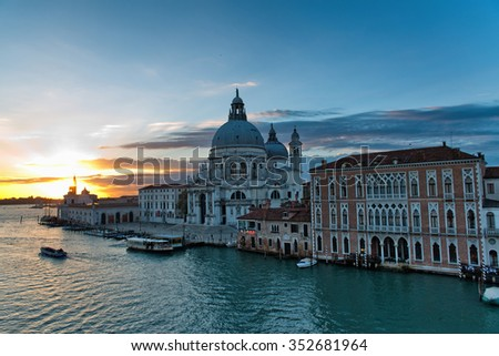 The Grand Canal, Venice at sunset with the orange sun setting behind the Basilica Santa Maria dell Salute and a vaporetto, or water bus, pulled up at the dock in front embarking passengers