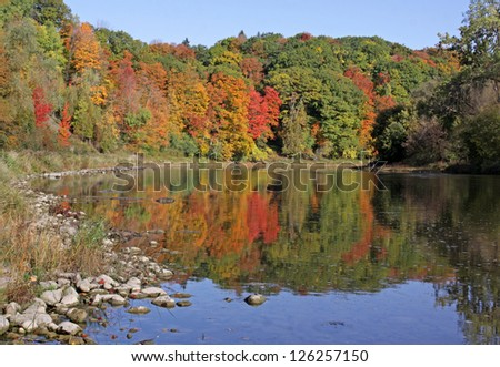 The Grand River with the fall colours reflecting in it.  Shot in Kitchener, Ontario, Canada. - stock photo