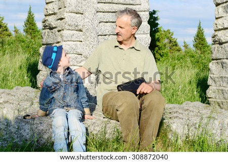 The grandfather talks to the grandson - stock photo