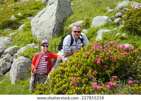 the grandfather with grandson resting on the rocks in the mountains - stock photo