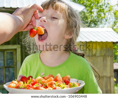 The grandmother feeds the granddaughter with strawberry - stock photo