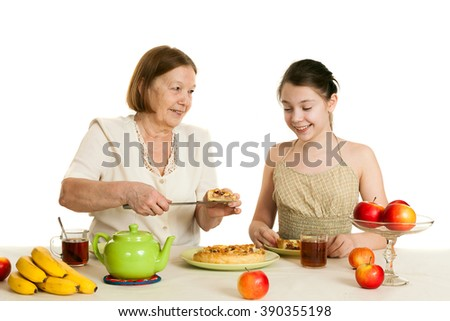 the grandmother treats the granddaughter with pie at a table
