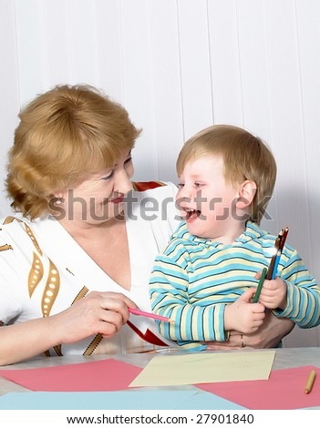 The grandmother with grandson is engaged behind a table