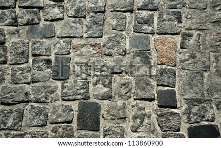 The granite block pavement of the old street is photographed close-up. - stock photo