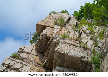 The granite rock and sky with clouds on background. - stock photo