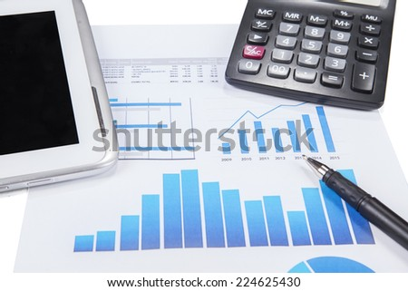 The graph of marketing report with pen, calculator, and a digital tablet on the table - stock photo