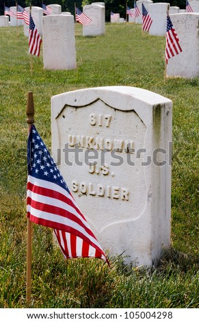 The grave of an unknown US soldier marked with  a flag on Memorial Day. - stock photo