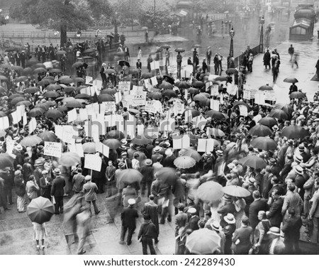 The Great Depression. A crowd of depositors protest in the rain at the Bank of United States after its failure. Signs demand bank stockholders be taxed to repay small depositors. New York City 1931.