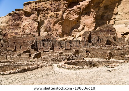 The Great House nestles beside the huge sandstone cliffs at Chaco Canyon. - stock photo