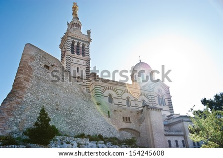 The great neo-byzantine architecture of the Notre-Dame de la Garde with the ruins of old fortress looks scenic in morning sunbeams, Marseille, France. - stock photo