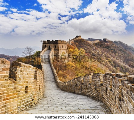 The Great wall of China ancient national architectural landmark high in Mutianyu mountains under blue sky tracing away - stock photo