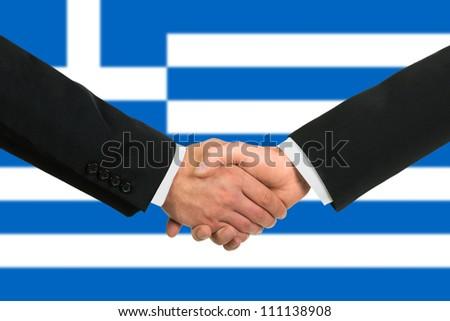 The Greek flag and business handshake - stock photo