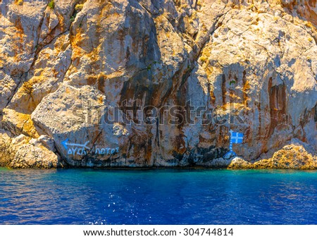 The Greek flag painted on the rocks in Symi island in Greece