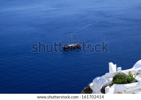 The Greek volcanic island of Santorini, is known as a top vacation destination. It is famous for its  blue domed churches, the majestic sunset, the steep cliffs, and the unique architecture. - stock photo