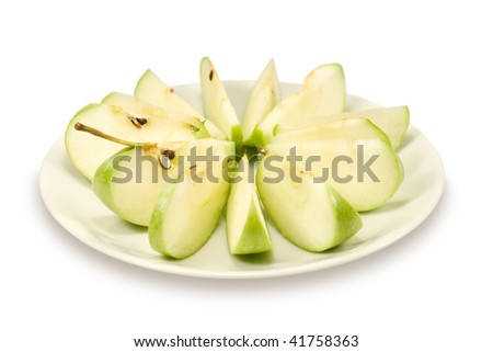 The green apple cut on small segments lays on a white porcelain plate. On a white background - stock photo