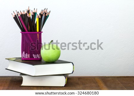 the green apple with pencil box on wooden table in concept of study or back to school with concrete wall background - stock photo