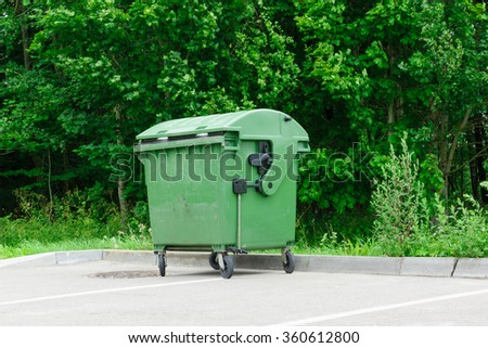 the green garbage container costs on an automobile parking - stock photo