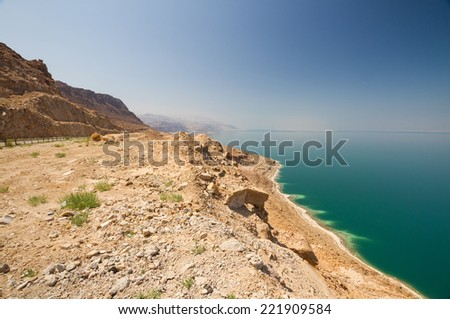 The green water of the land-locked Dead Sea in Jordan, with a view to the Israeli side. - stock photo