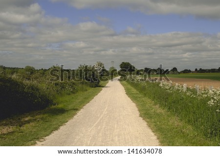 the greenway - disused railway line now a cycleway. stratford upon avon warwickshire. agricultural fields and farmland on either side. - stock photo