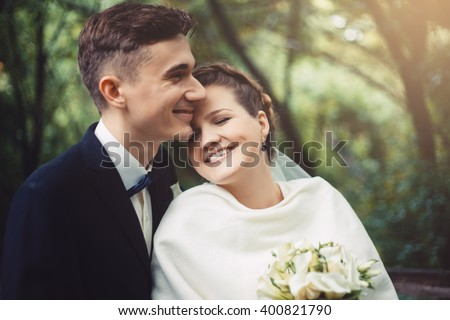 The groom and bride are walking in the park at their wedding day. Groom and bride are embracing. Couple are smiling, they are happy.  Newlyweds in love. They became husband and wife this day. - stock photo
