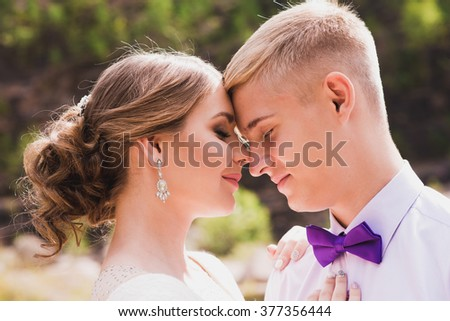 the groom and the bride against rocks. newlyweds on wedding walk. gentle relations. beautiful newlyweds. beautiful newlyweds in park.groom and bride.the groom and the bride against the wood. - stock photo