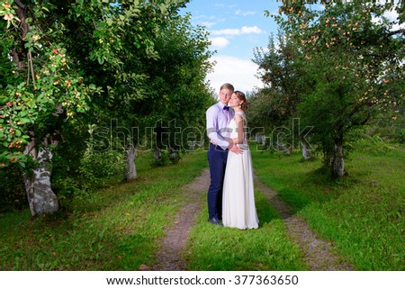the groom and the bride against rocks. newlyweds on wedding walk. gentle relations. beautiful newlyweds. beautiful newlyweds in park. groom and bride.beautiful couple.newlyweds against the blue sky. - stock photo