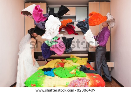 The groom and the bride collect things in a bedroom - stock photo