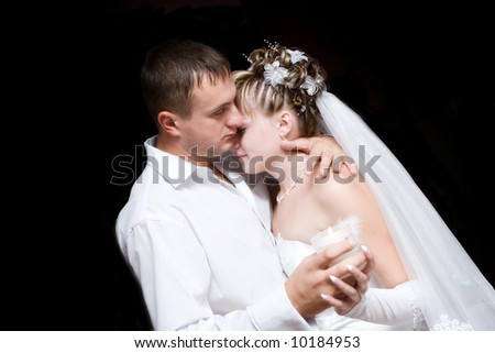 The groom and the bride dance with a burning candle in hands - stock photo
