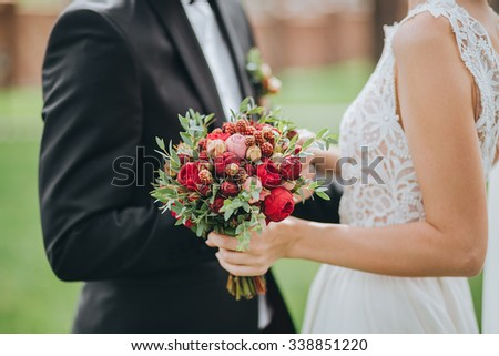 the groom and the bride dressed in white dress standing and holding a bouquet of red flowers and greenery