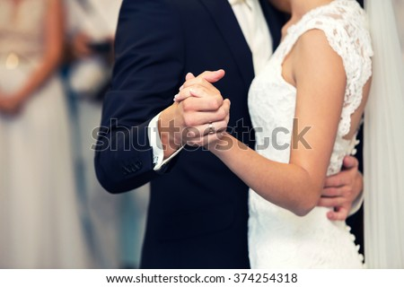 the groom and the bride hold each other by hands - stock photo