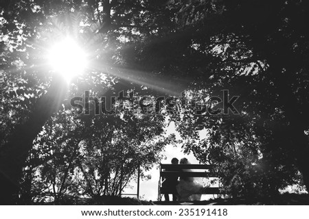 The groom and the bride in day of the wedding sit in park on a bench - stock photo