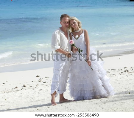 The groom and the bride on the tropical beach. - stock photo