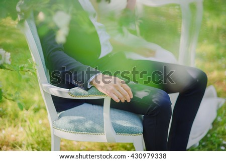 the groom and the bride sit on a small sofa in the blossoming apple-tree garden