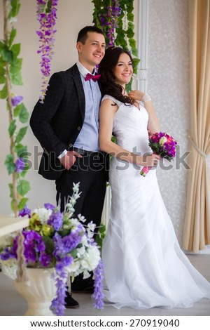 The groom embraces the bride, close to the vine - stock photo