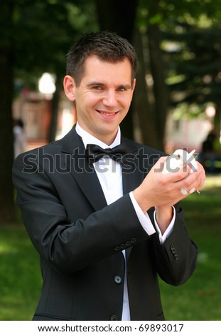 The groom has control over a white pigeon