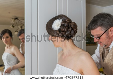 The groom helps the bride to dress / wedding / bridal couple
