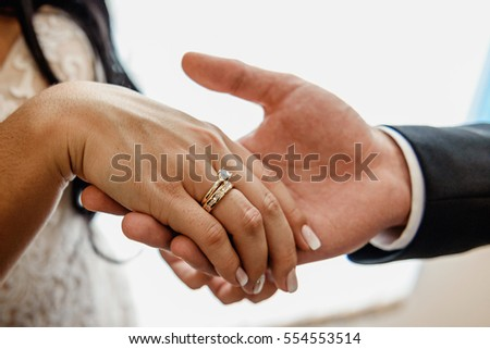 The groom holds his bride's hand